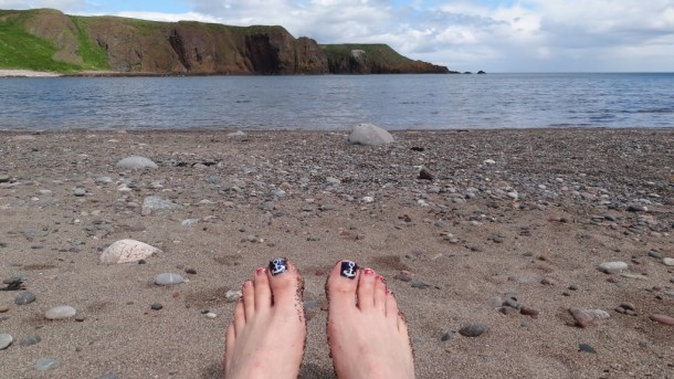 toes with a beach and cliffs in the background