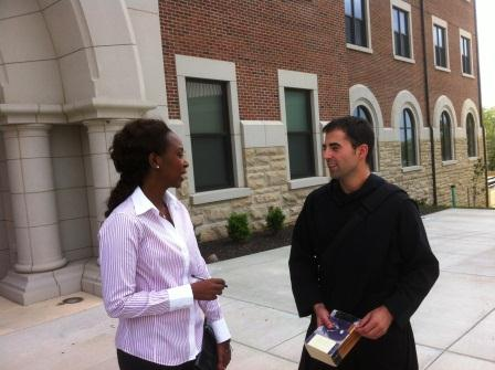 Immaculee chats with a monk from St. Benedict's Abbey on campus.