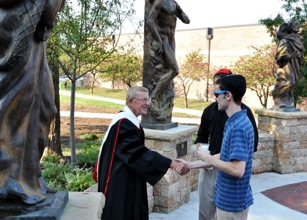 4. Lou Holz greets Benedictine College freshmen in 2012 at the campus Raven Crossing beneath Frederick Hart statues of St. Peter, Adam and St. Paul.