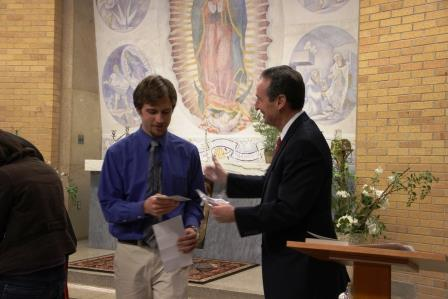 In Benedictine College's Guadalupe Chapel, President Stephen D. Minnis gave certificates and medals to students consecrating themselves to Mary.