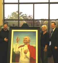 Chaplain Fr. Rolling, Dr. Linda Henry and President Minnis unveil Benedictine College's new portrait in the St. John Paul II Student Center.