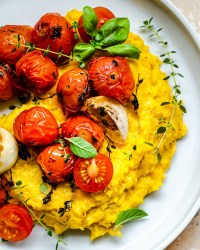 Polenta with roasted tomatoes on white plate