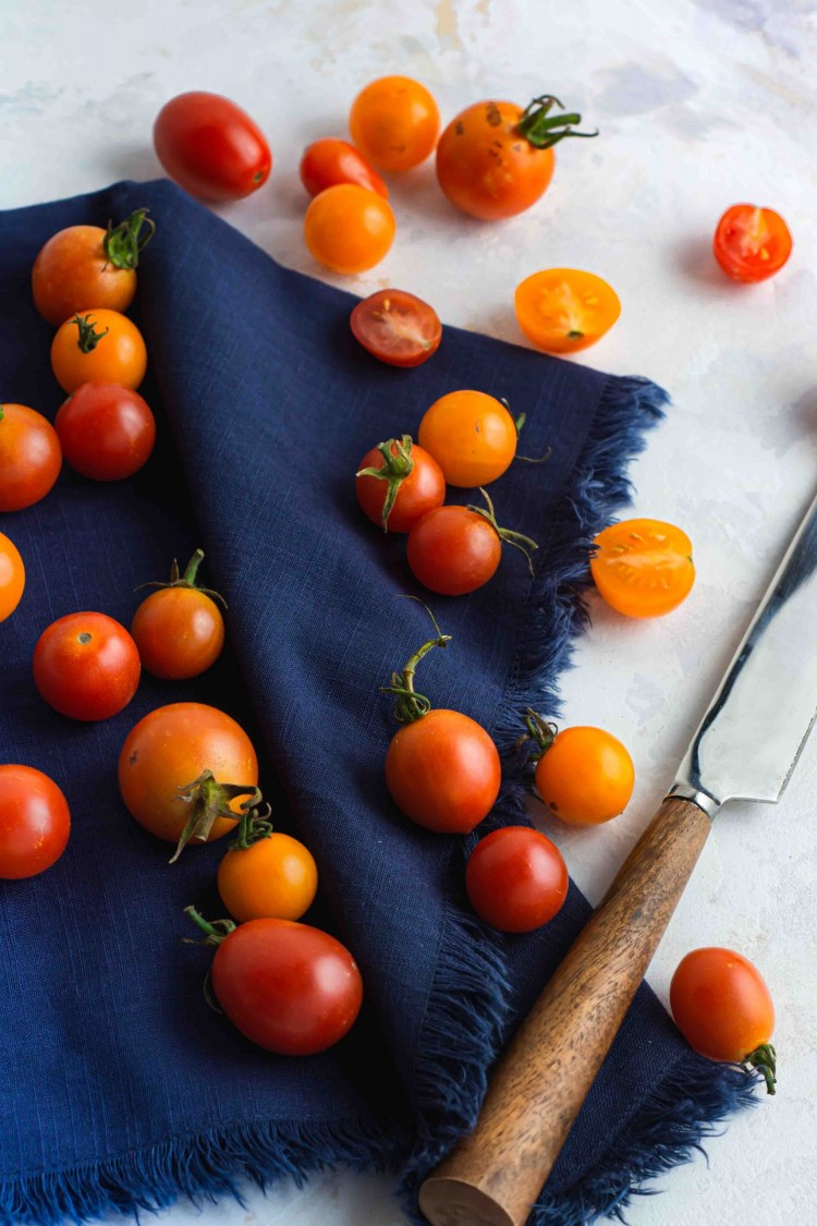 Cherry Tomatoes on a blue napkin with a knife