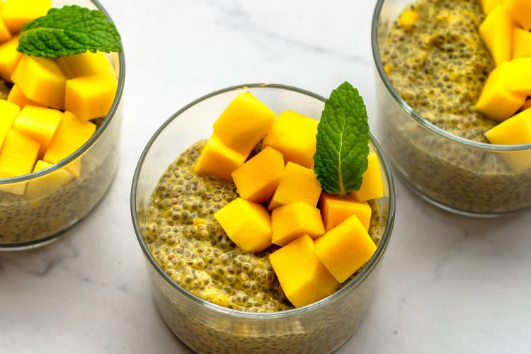 three cups of mango chia pudding with chopped mango as topping