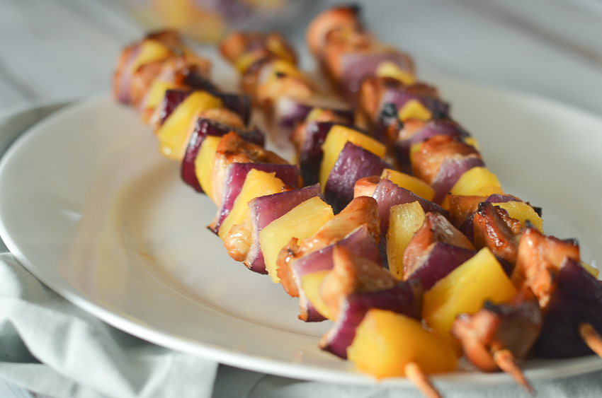 These pineapple chicken kabobs are fantastic for anyone looking for a fun party recipe, or can be made for a family dinner in the oven simply by baking and broiling! The chicken is marinated in a pineapple honey sauce and then placed on the skewer between layers of red onion and pineapple. Paleo, gluten-free, grain-free, refined sugar free.