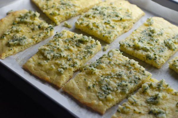 Looking for some super low-carb bread to accompany any meal? This Parmesan garlic flatbread is delicious and less than 1 net carb per slice! Keto, gluten-free, grain-free, primal.