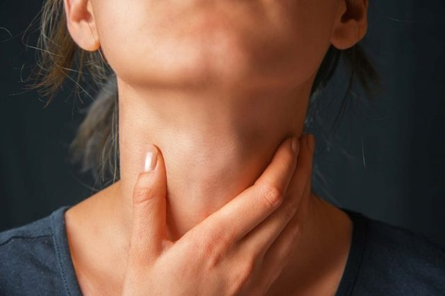 Woman feeling her throat with her hand.
