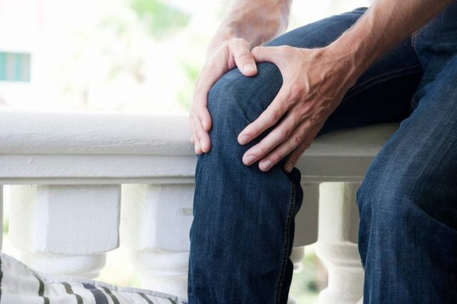 Man in jeans holding his knee.