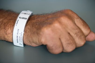a hand of a person with a hospital bracelet