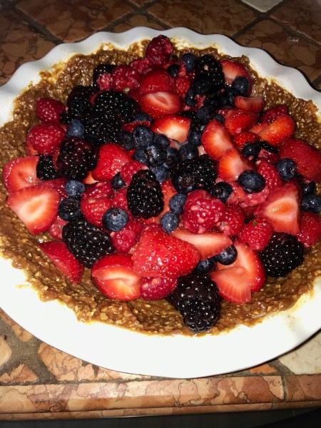 Pie with blackberries, strawberries, blueberries that has a walnut and date crust.