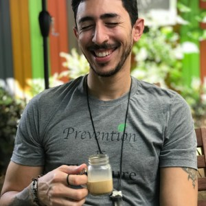 hispanic male holding coffee, laughing and wearing a gray prevention shirt