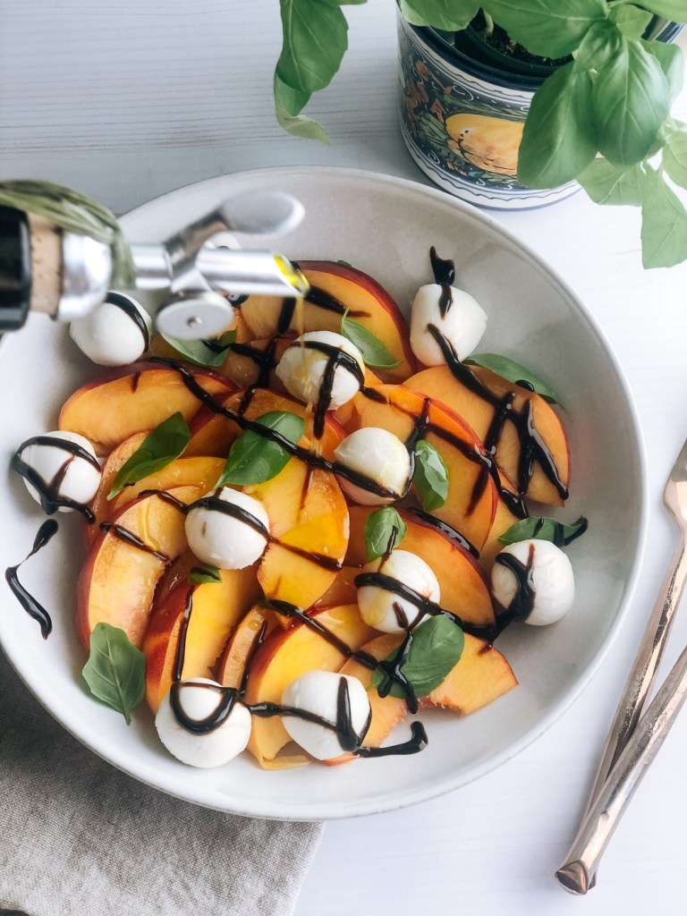 Drizzling olive oil over simple peach caprese salad