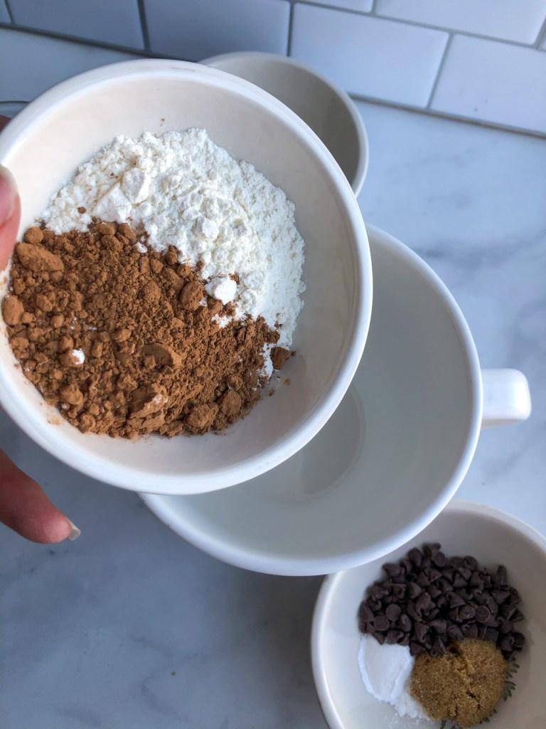 adding cocoa powder and flour into mug