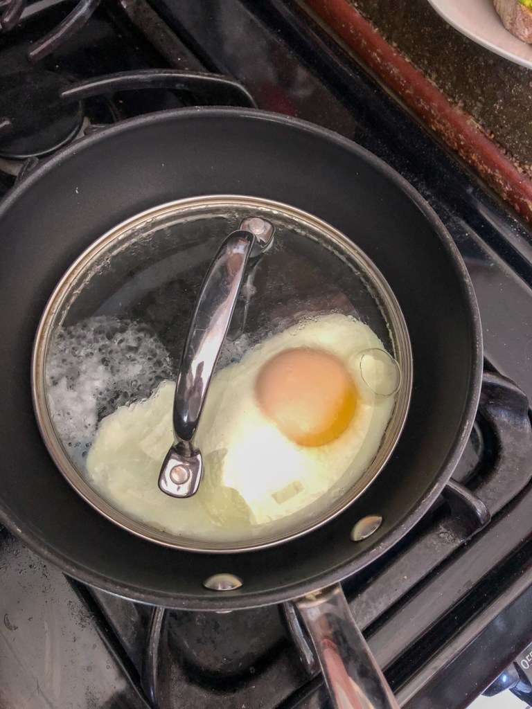 Covered egg in pan with opaque film starting to cover the yolk