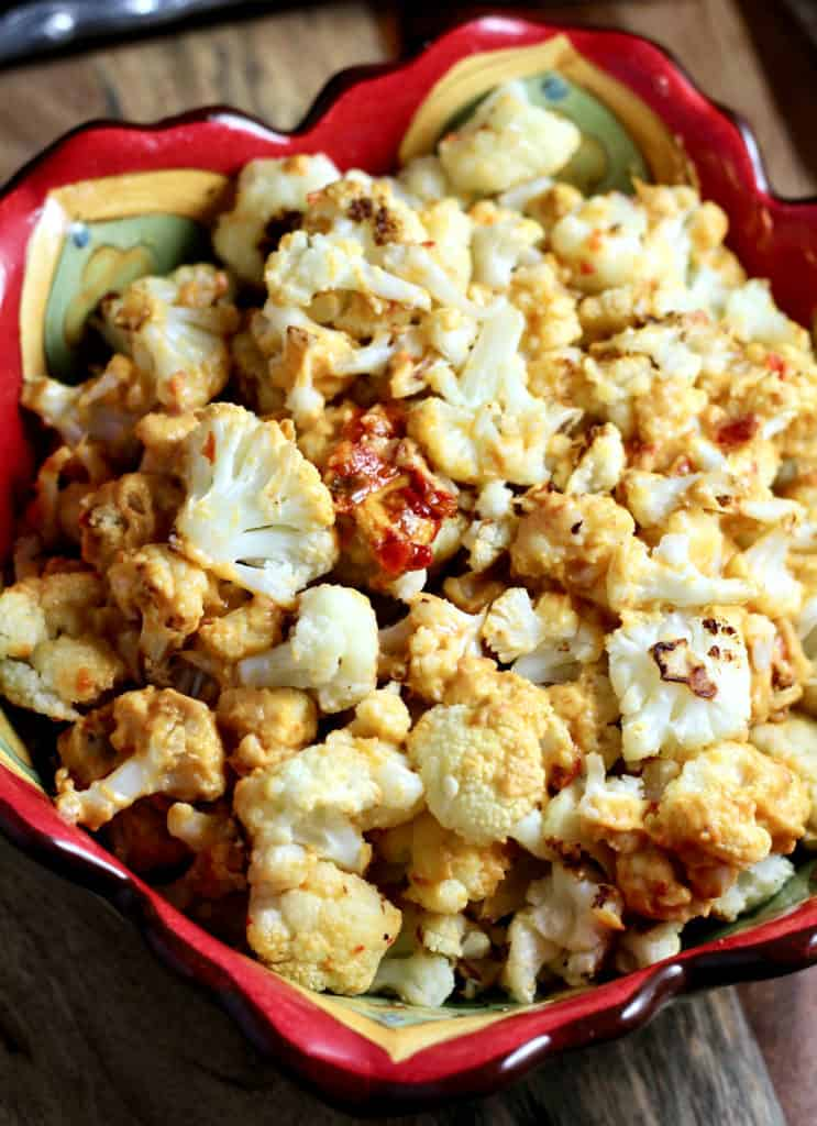 Bowl of roasted cauliflower tossed in red pepper hummus