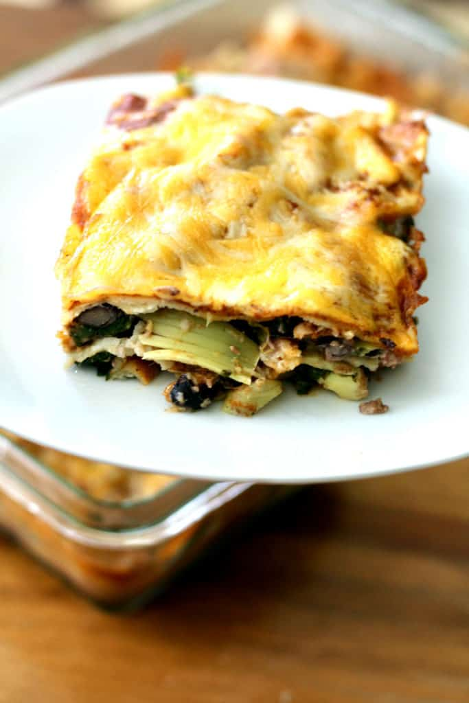 Slice of spinach artichoke stacked enchilada