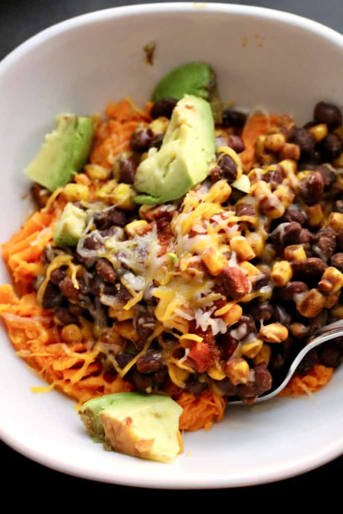 Vegetarian mexican sweet potato bowl with melted cheese and avocado