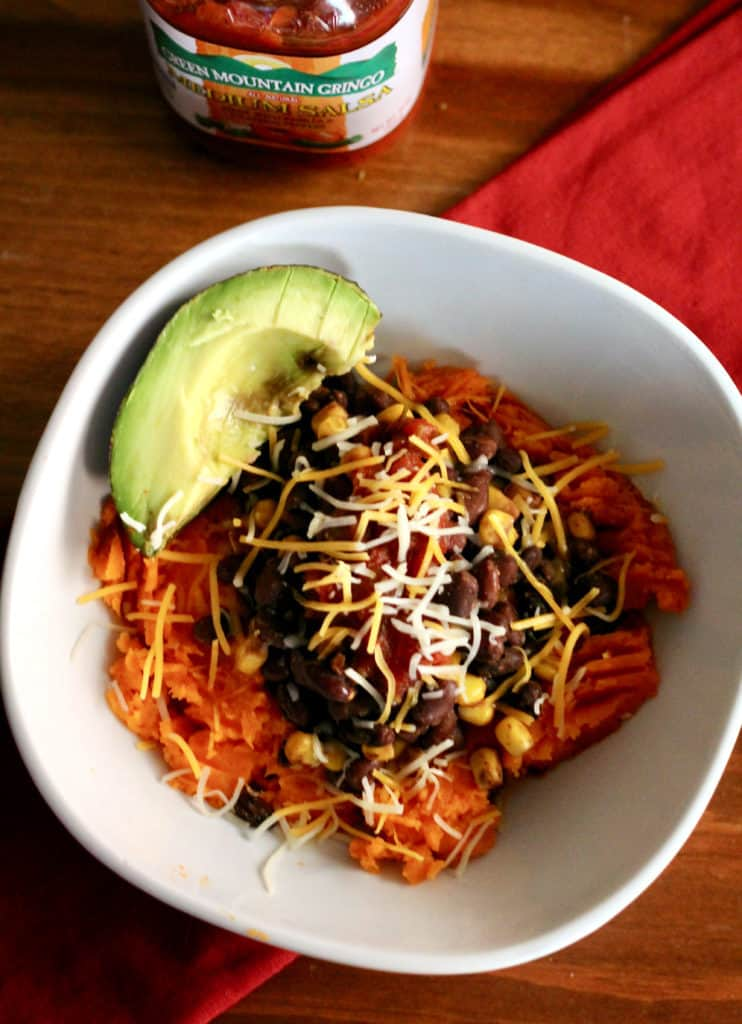Mexican sweet potato bowl with shredded cheese and avocado
