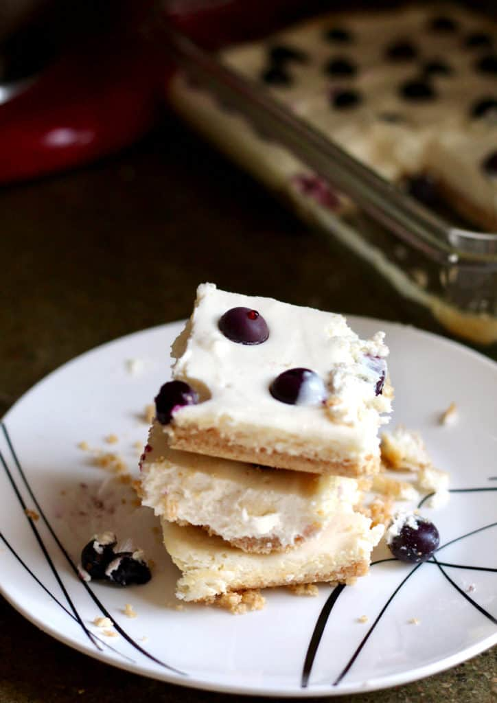 Stack of light and lemony blueberry cheesecake bars