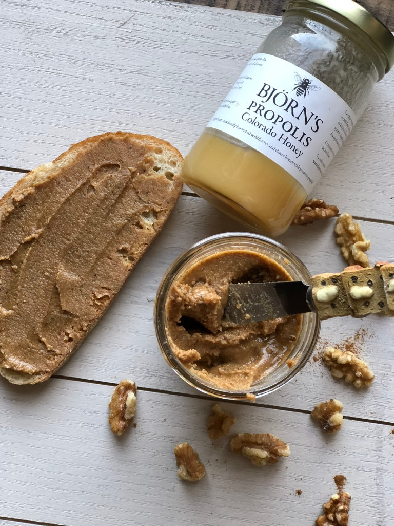 Jar of walnut butter, slice of toast with walnut butter spread on top, and jar of Bjorns honey