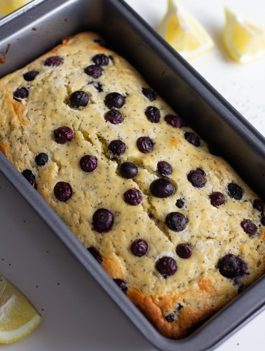 Healthy Lemon Blueberry Bread in loaf pan with lemon wedges on the side