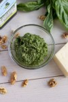 Bowl of homemade walnut pesto with walnuts, fresh basil, and parmesan cheese in the background