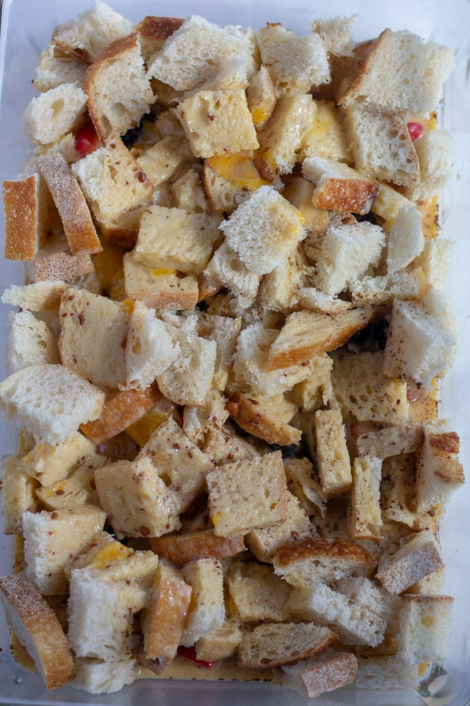 Egg mixture poured over bread cubes