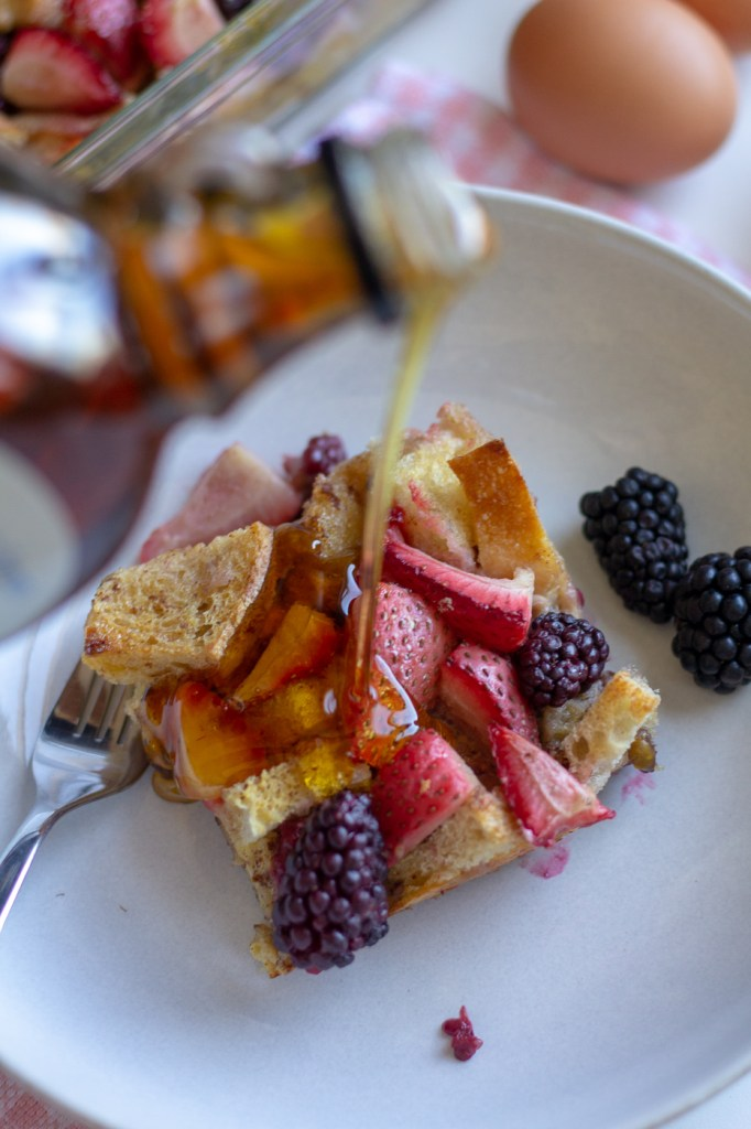 Pouring maple syrup over berry french toast casserole