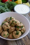 Bowl of healthy kale turkey meatballs with side of lemon greek yogurt sauce