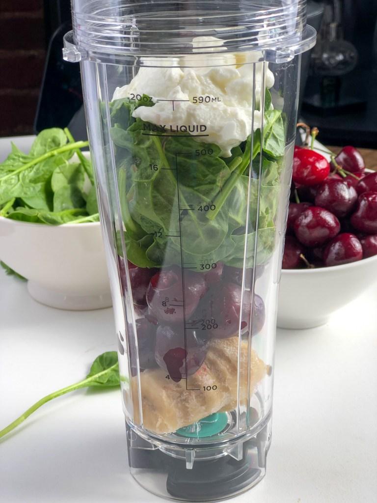 Frozen bananas, fresh cherries, spinach and greek yogurt in a blender