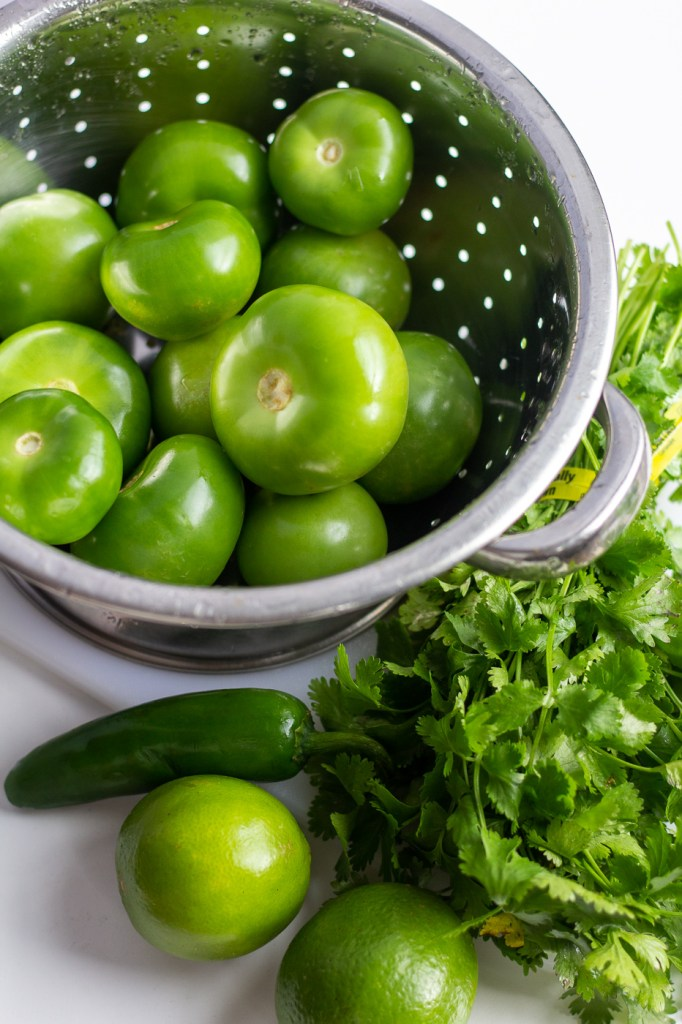 Pile of bright green tomatillos, green limes, jalapeno and fresh cilantro