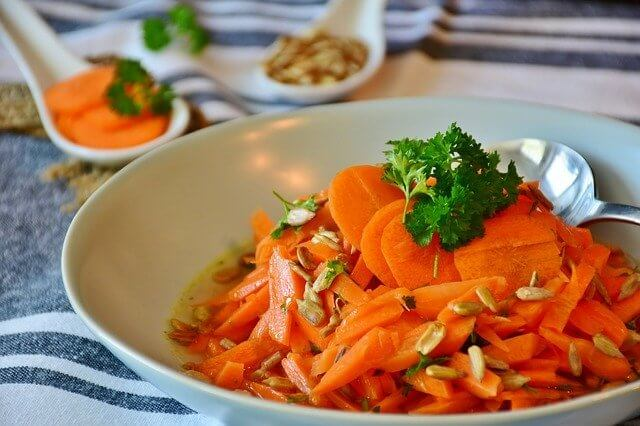 Bowl of sliced carrots with sunflower seeds