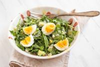 Bowl of greens with eggs and avocados