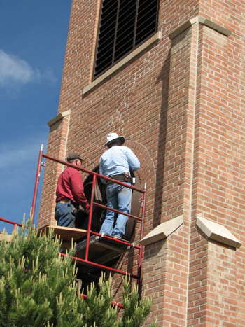 Jim Ruckman, right, installed a new window last month outside of the choir loft at Holy Family Catholic Church in Meeker, replacing the original one. The church was built in 1912.