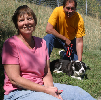 """Susan Sammons, plant manager, and employee Glenn Abbott, who rescued Buddy, have """"adopted"""" the dog as the plant's mascot."""