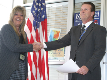 Caryl Meitler receives congratulations Nov. 13 from Murray Johnson, manager of post office operations out of Grand Junction.