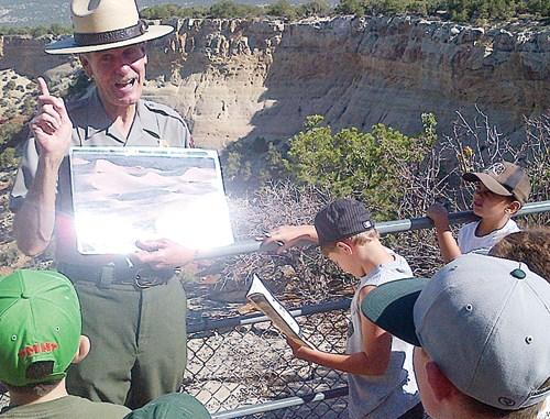 Ranger Randy explains to junior rangers how the Dinosaur National Monument was formed.