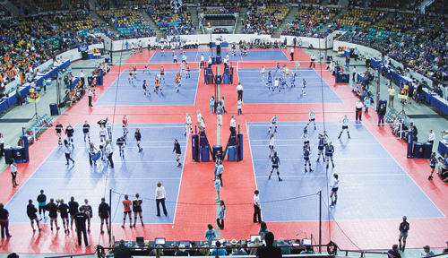 The Meeker High School varsity volleyball team is pictured playing on one (bottom right) of five courts in the Denver Coliseum.