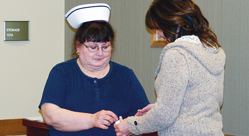 Registered nurse Anne Benhart, left, prepares to pin Ruth King's granddaughter, Jennifer Turner, with the Ruth King Excellence in Nursing Award. King, former nursing director Mary Reese and longtime Rangely District Hospital nurse Sheryl Sheley were the first recipients of the award — King and Reese posthumously. Chief nursing officer Sharma Vaughn said that King, a registered nurse who worked for Rangely Community Hospital and RDH in their fledgling years and for decades afterward, passed on a legacy of professionalism and care to generations of RDH nursing staff.