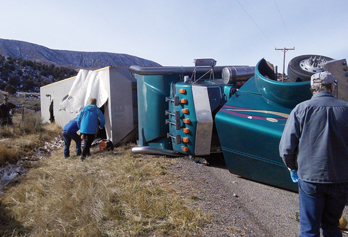 Friends and neighbors help cut through the top of this cattle-filled truck after the rollover on Dec. 2 on County Road 7 west of Meeker. One cow was killed outright in the rollover accident and injuries resulted in the euthanization of three other animals.