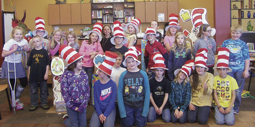 Read Across America was celebrated the week of March 2-6 at Meeker Elementary School. During library, the students learned about Theodore Seuss Giesl and his love of illustrating and writing books for children. Seuss' birthday party was held on March 2. To start the day, 26 high school Life Skills students read a Seuss book to each class. Shana Holliday's marimba band performed as everyone came in and settled down and  Kathleen Kelley's high school English literature class performed four Dr. Seuss books in reader's theater. Pictured above is Renay Mobley's fourth-grade class in the library.