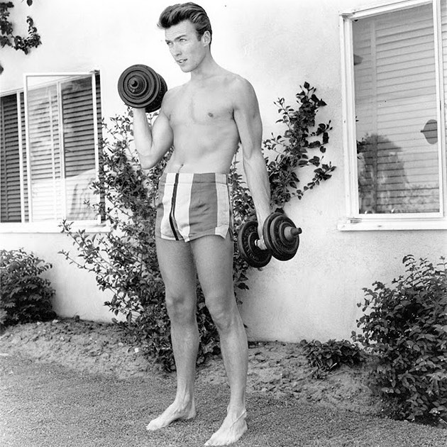 A 26 years-old Clint Eastwood works out with dumbbells at home in June 1956, Los Angeles