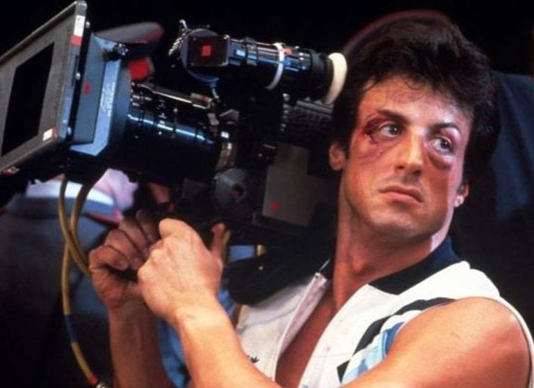 Sylvester Stallone behind the scene of 'Rocky IV' (1985). Still with his make-up and operating a camera.