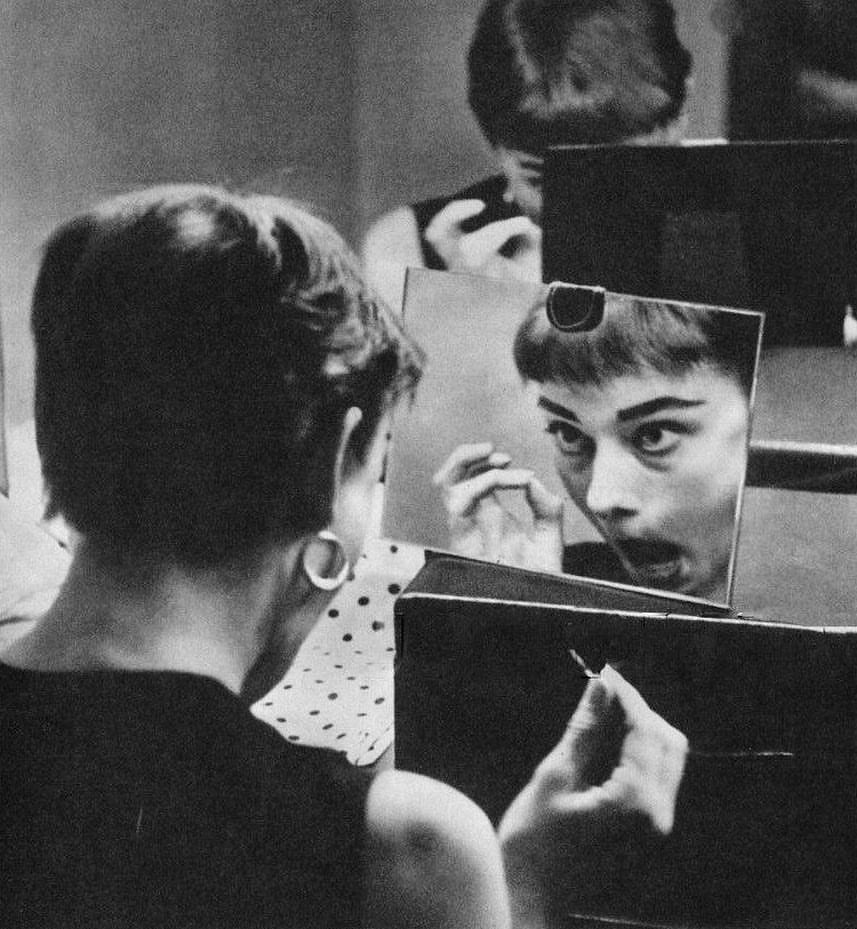 Audrey Hepburn applying makeup in her dressing room, 1954