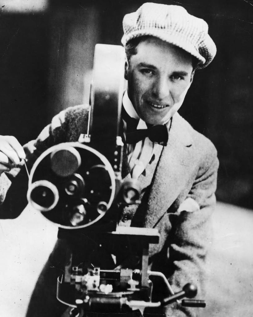 Charlie Chaplin, english actor and director operating a movie camera in 1918