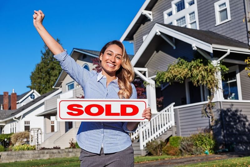 a cheerful young women with a red SOLD sign in front of a row of houses
