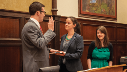 Eugene Ang/The Hoya GUSA President Nate Tisa (SFS '14) was sworn in by predecessor Clara Gustafson (SFS '13) as outgoing Vice President Vail Kohnert-Yount (SFS '13) looked on Saturday.