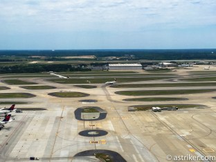 A 757 holding short as another plane departs, shadow of departure caught on the ground.