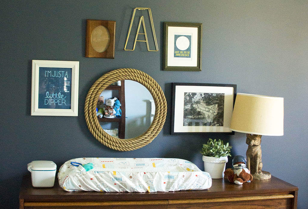 Baby Andrew's space cowboy themed nursery. Vintage dresser with space-themed art against dark wall.