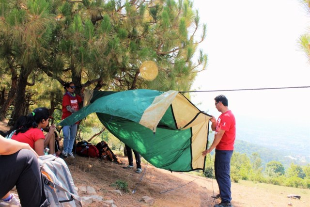 Instructors training children to set up a tent